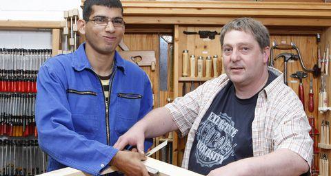 Zwei Männer in Arbeitskleidung verarbeiten ein Holzprodukt