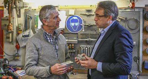 Ein Werkstattmitarbeiter schüttelt einem Kunden die Hand.