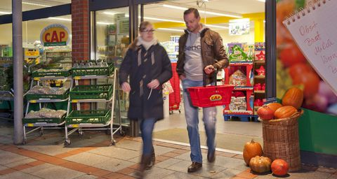 Zwei Besucher verlassen mit ihren Einkäufen den Cap-Markt