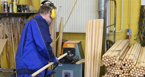 Mann bedient eine Holzstielfräse