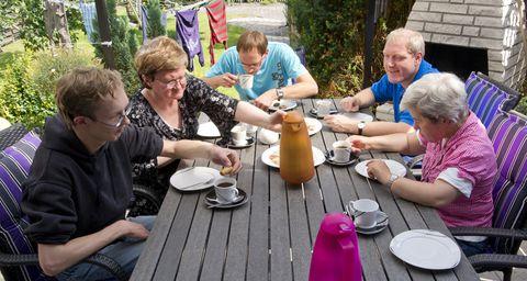 Bewohner einer Wohngruppe sitzen zusammen bei Kaffee und Kuchen