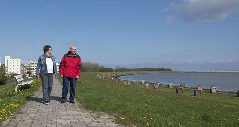 Eine Frau und ein Mann gehen am Meer entlang spazieren