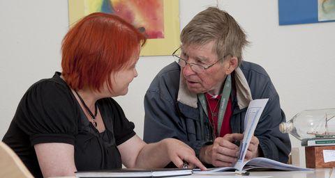 Eine Altepflegerin und ein Senior im Dialog