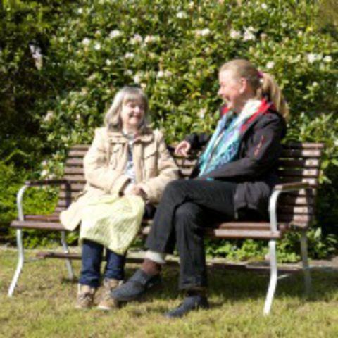 Zwei Frauen unterhalten sich auf einer Gartenbank