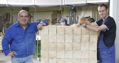 Zwei Männer in Arbeitskleidung stehen neben einem Stapel verarbeiteter Holzprodukte