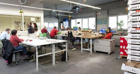 Mitarbeiter sitzen an ihren Arbeitsplätzen in der Montage