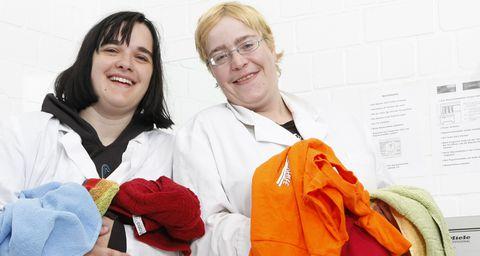 Zwei Frauen waschen Wäsche in der Wäscherei