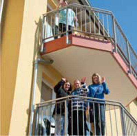 Bewohner einer Wohngruppe stehen winkend auf ihrem Balkon
