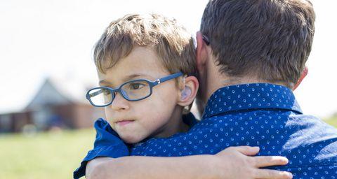 kleiner Junge blickt über den Arm eines Betreuerss