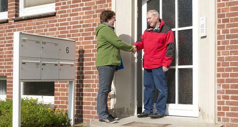 Eine Frau begrüßt einen Mann an der Tür