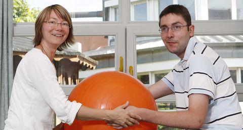 Eine Frau und ein Mann machen Übungen mit einem Gymnastikball
