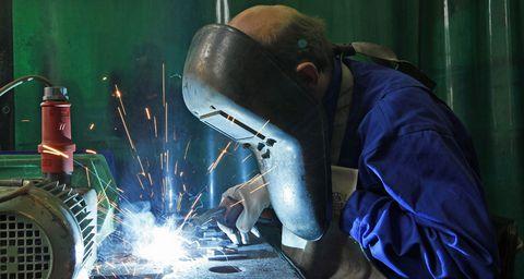 Mann beim Arbeiten mit dem Schweißgerät