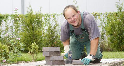 Ein Mann pflastert die Terrasse