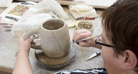 Eine Frau zeichnet ein Muster in einen Krug aus Ton