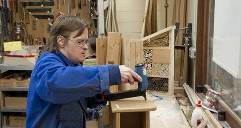 Ein Mann in Arbeitskleidung bearbeitet eine Holzplatte