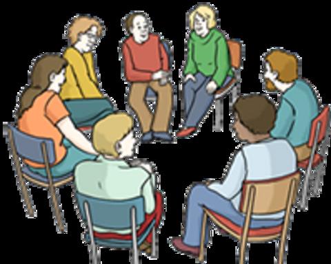 Ehrenamtliche Mitarbeiter sitzen in einem Stuhlkreis zusammen