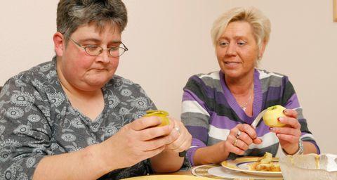 Zwei Frauen schälen Äpfel