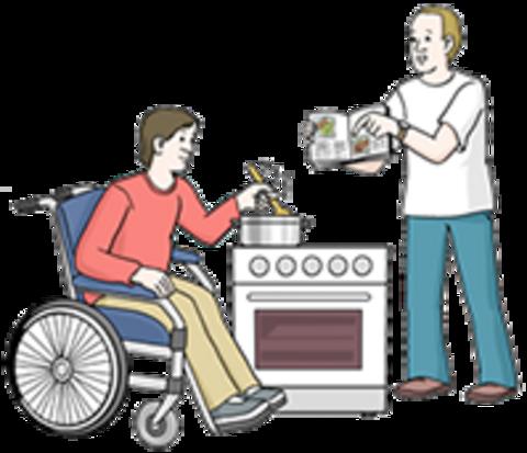 Ein Betreuer unterstützt einen Rollstuhlfahrer beim Kochen