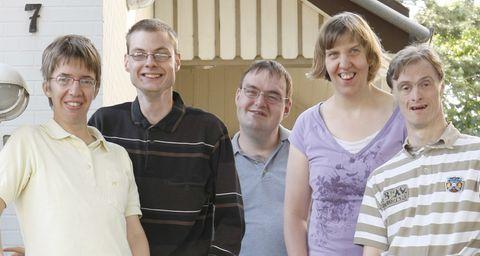 Bewohner einer Wohngruppe schauen lachend in die Kamera