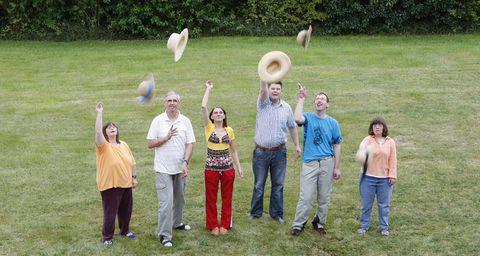 Mehrere Personen stehen auf der Wiese und werfen ihre Hüte in die Luft