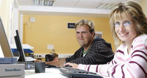 Zwei Menschen sitzen vor einem Computer