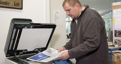 Ein Mann kopiert etwas am Drucker