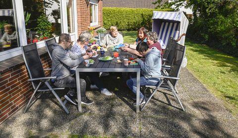 Menschen sitzen gemütlich auf der Terrasse und essen