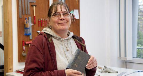Eine Frau hält ein frisch gebundenes Buch in der Hand