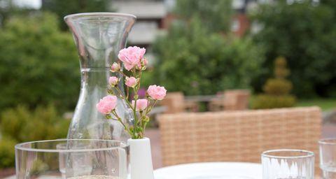 Eine Vase mit Blumen steht auf einem Gartentisch