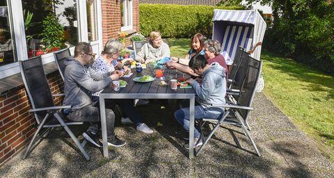Menschen sitzen gemütlich auf einer Terrasse zusammen