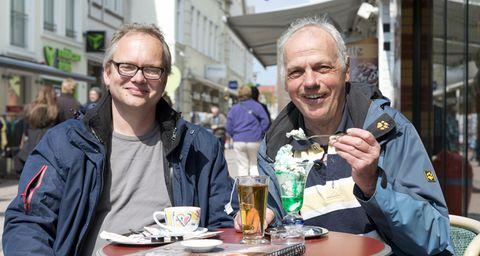 Zwei Männer sitzen im Café und essen ein Eis