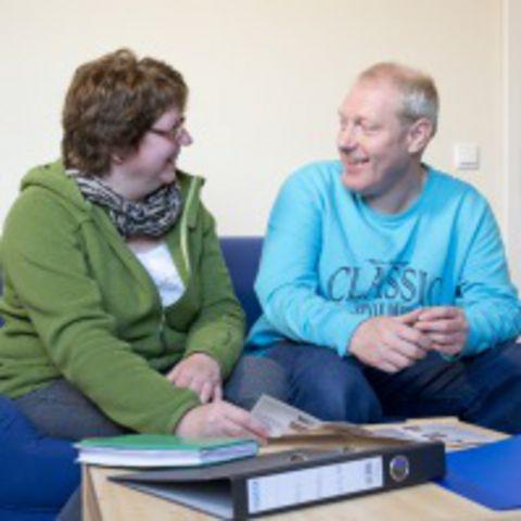 Eine Frau und ein Mann unterhalten sich auf einem Sofa