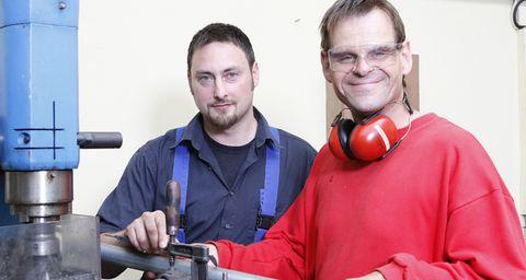 Zwei Männer in Arbeitskleidung arbeiten mit einer Werkzeugmaschine