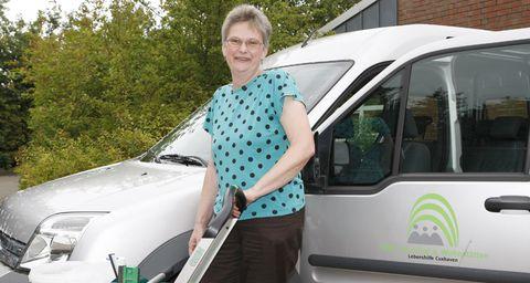 Eine Frau steht mit ihren Arbeitsgeräten vor dem Firmenwagen